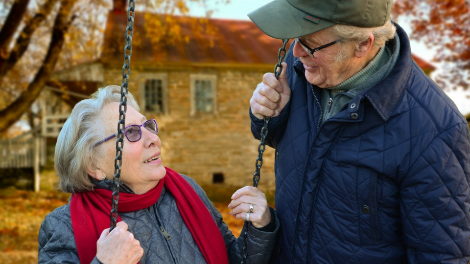 elderly couple sitting on a swing