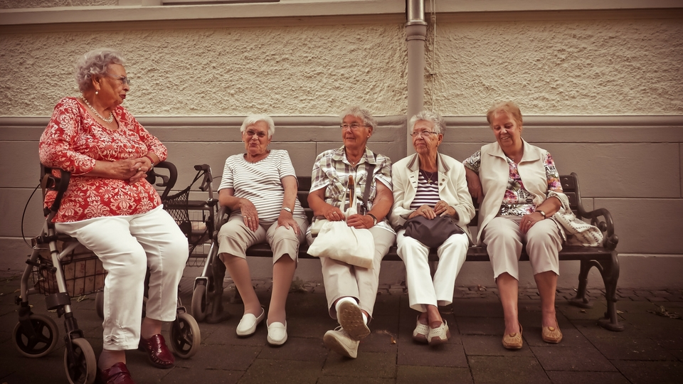 elderly women sitting on a bench