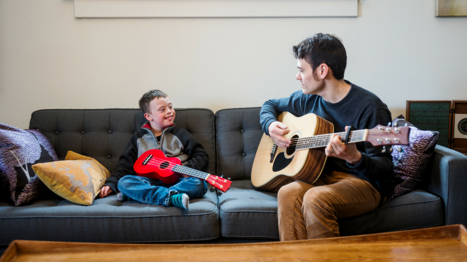 music therapist and child playing guitar