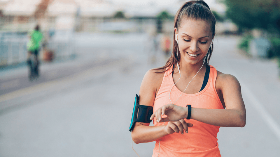 woman runner looking at her fitbit