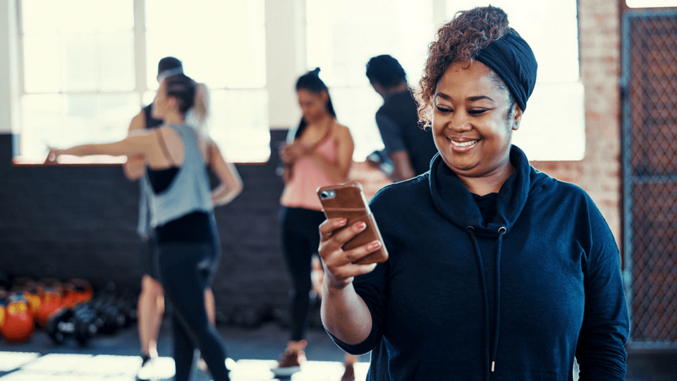 woman using at fitness app on her smart phone in gym class