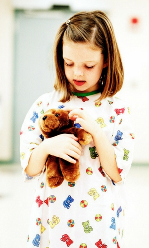 Girl in Hospital Gown Holding Teddy Bear