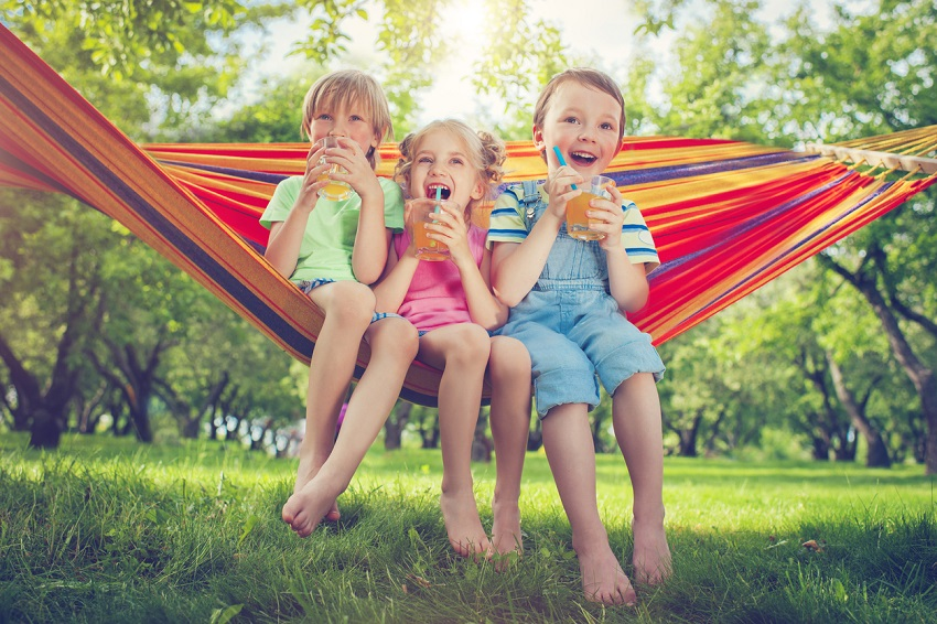 group of young children drinking juice on hammock