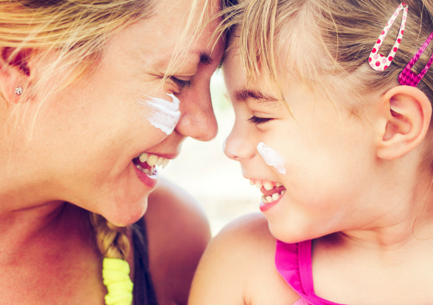 mom-and-daughter-smiling-with-sunscreen-on-their-cheeks